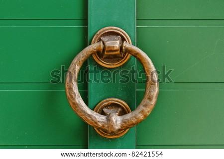brass knocker on the green door - stock photo