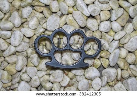 Brass knuckles on crime scene ground - stock photo