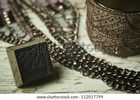Brass, leather and metal jewelry on an old grungy table - stock photo