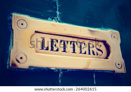 Brass letter box in old painted door, close-up, toned image - stock photo
