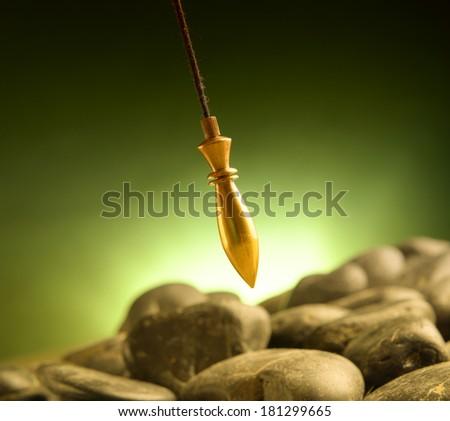 Brass pendulum, tool for dowsing. - stock photo