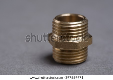 Brass plumbing nipple on grey surface - stock photo