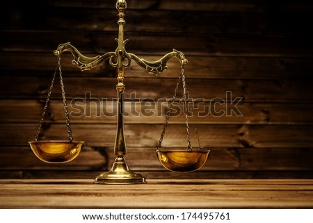 Brass scales over wooden background  - stock photo