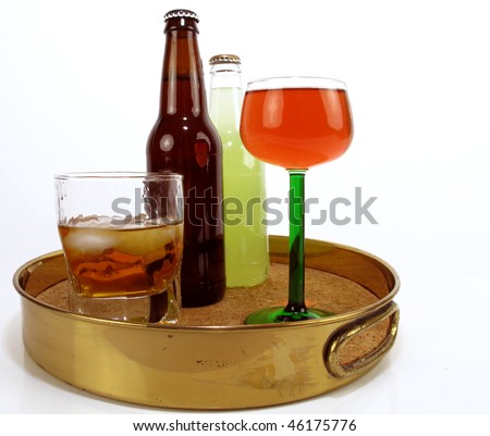 Brass serving tray with assorted adult beverages - stock photo