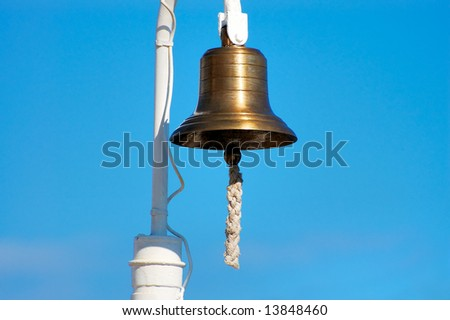 Brass ship's bell with thick rope hanging - stock photo