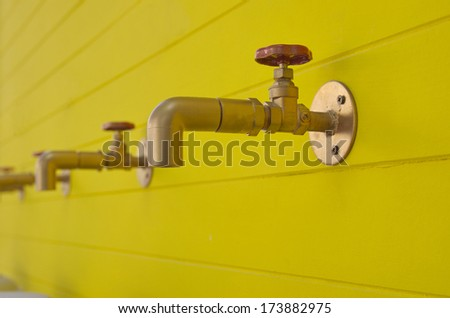 brass taps on yellow wall