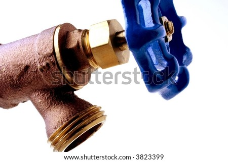 Brass water faucet with blue handle against white background. - stock photo