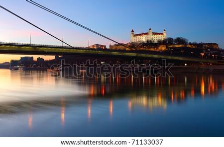 Bratislava castle and novy bridge at sunset with reflection - stock photo