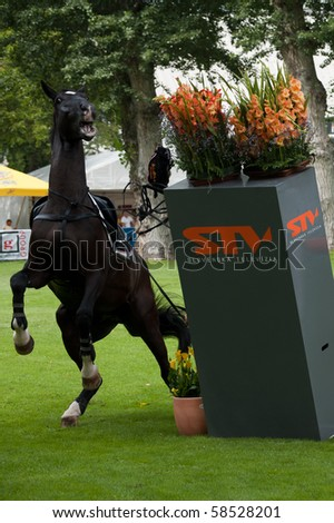 BRATISLAVA, SLOVAKIA - AUGUST 5: OTSCHMAIER Wolfgang on horse ROYAL KING OF DARKNESS fails on first hurdle during qualification to Grand Prix CSIO-W*** August 5, 2010 in Bratislava, Slovakia - stock photo