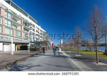 BRATISLAVA, SLOVAKIA - JANUARY 6, 2015: People on walkway next to shore of Danube river with Apollo bridge in the background. - stock photo