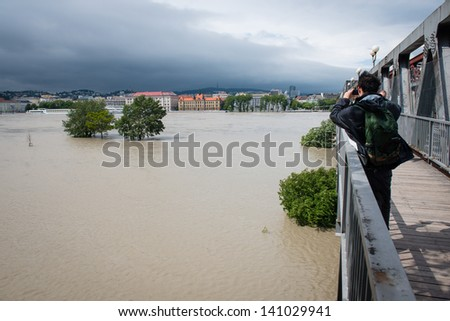 BRATISLAVA, SLOVAKIA - JUNE 4:  Man photographs increasing level of the Danube river from the Old Bridge on June 4, 2013 in Bratislava - stock photo