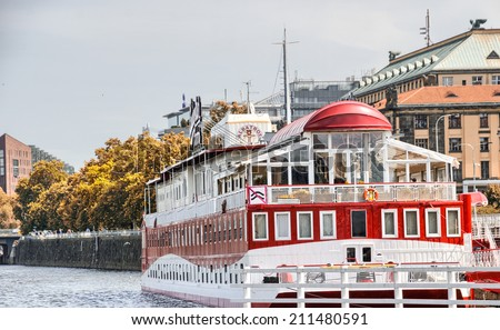 BRATISLAVA, SLOVAKIA - JUNE 24, 2011: Red cruise ship anchored on Vlatava river. Cruising from Bratislava to Vienna is a famous way of visiting both cities. - stock photo