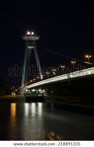 BRATISLAVA, SLOVAKIA - JUNE 09, 2014: The night view of The Most SNP bridge on Danube river with the exposition of photographs. - stock photo