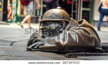 BRATISLAVA, SLOVAKIA - MAY 5. Cumil (The Watcher) or Man at work - statue of man peeking out from under a manhole cover in Bratislava, Slovakia. Popular attraction was made in 1997 by Viktor Hulik. - stock photo