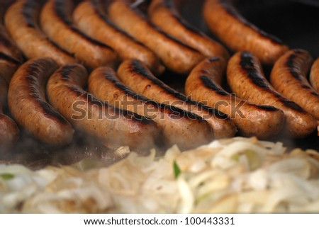 Bratwurst sausages with onions and peppers cooking on grill with smoke and heat blur rising up