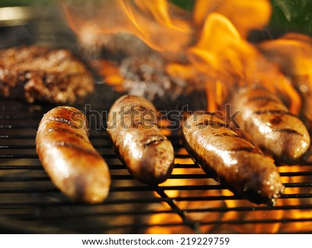 bratwursts cooking on flaming grill - stock photo