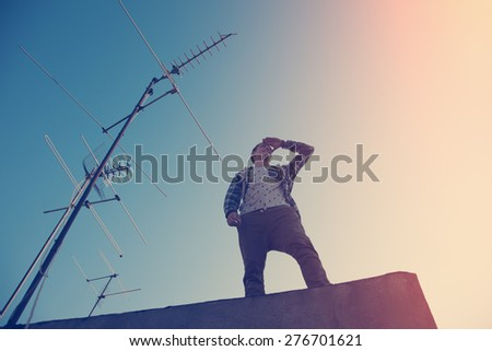 Brave and handsome traveler standing on high roof and looking far away (intentional sun glare and vintage color) - stock photo
