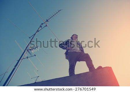 Brave and handsome traveler standing on high roof and looking far away over the city (intentional sun glare and vintage color) - stock photo