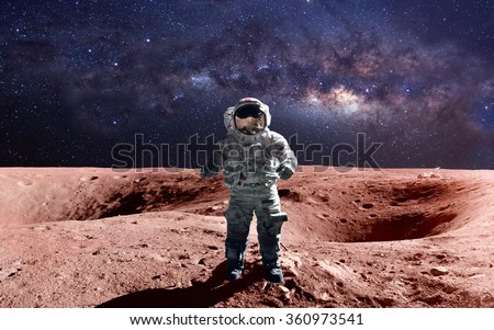 Brave astronaut at the spacewalk on the mars. This image elements furnished by NASA. - stock photo