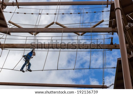 Brave boy conquering an obstacle course - stock photo