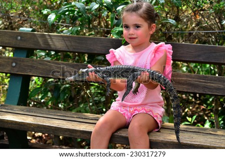 Brave child ( girl age 05) holds a young baby Australian Salt water crocodile. - stock photo