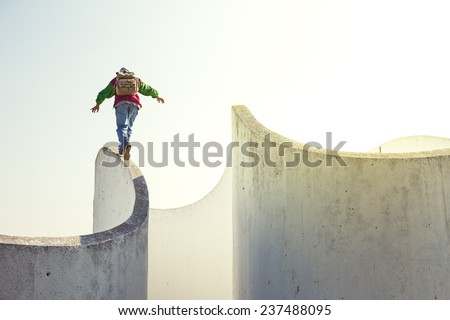 brave extreme man with backpack walking on a thin concrete wall - stock photo