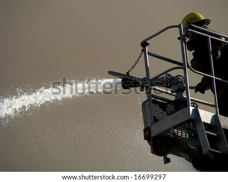 Brave fireman spraying water onto a large fire - stock photo