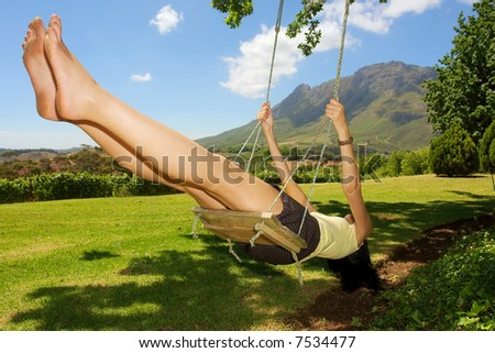 Brave girl (mulatto/colored) on swing - awesome mountains is a background. Shot near Stellenbosch, Western Cape, South Africa. - stock photo