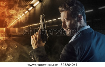 Brave handsome hero agent holding a gun and walking into the fire in an underground tunnel, danger and crime concept - stock photo