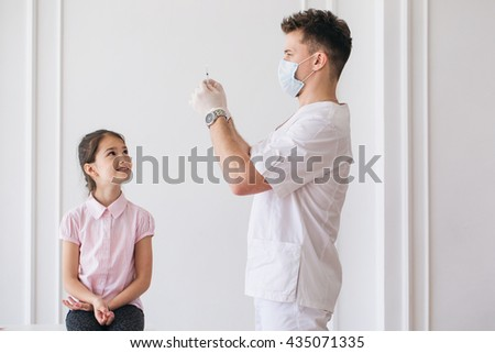 Brave little girl receiving injection in arm  in a hospital - stock photo