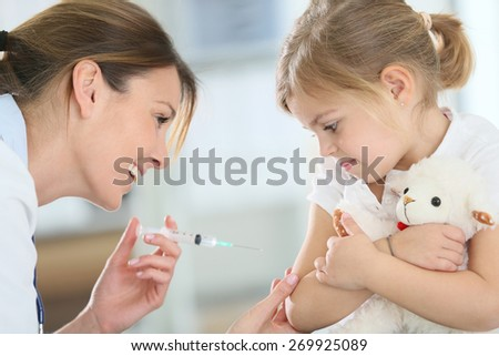 Brave little girl receiving injection in doctor's office - stock photo