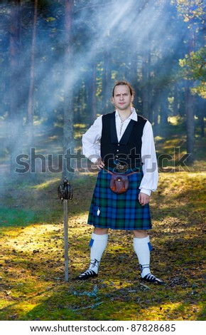 Brave man in scottish costume with sword in the forest - stock photo
