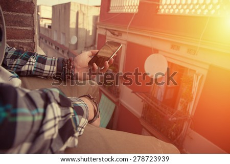 Brave man sitting on the edge of the roof with mobile phone in his hand (intentional sun glare) - stock photo