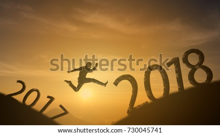 brave man successful concept,silhouette man jumping over the sun between gap of the mountain from 2017 to 2018 new year , it feel like a winner, success, finish,reach a goal of live, jobs,work