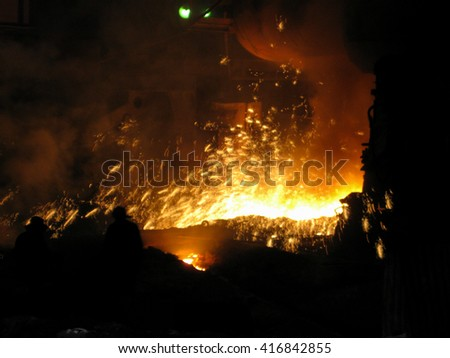 Brave men in metal fire sparks. Workers makes liquid metal in blast furnace. - stock photo