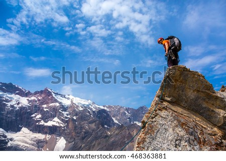 Brave Mountain Climber in bright shirt and helmet staying on sharp rocky peak and looking down