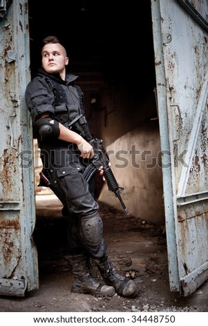 Brave sentinel with M4 carbine near the rusty gates. - stock photo