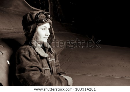 Brave young pilot resting against airplane, looking into distance. Room for copy space - stock photo