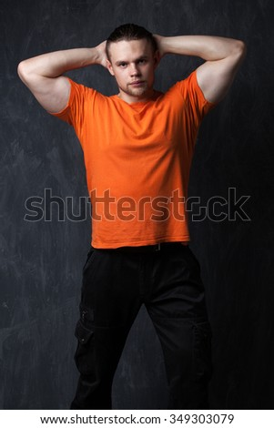 Brawny guy in the orange shirt holds his hands behind his head - the image on a gray background - stock photo