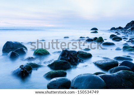 Bray Head rocks in the Irish Sea early morning cool blue long exposure image - stock photo