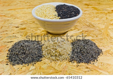Brayed black and white sesame and uncooked sesame in bowl - stock photo