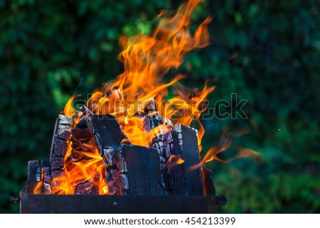 Brazier with burning coals on deep green background - stock photo