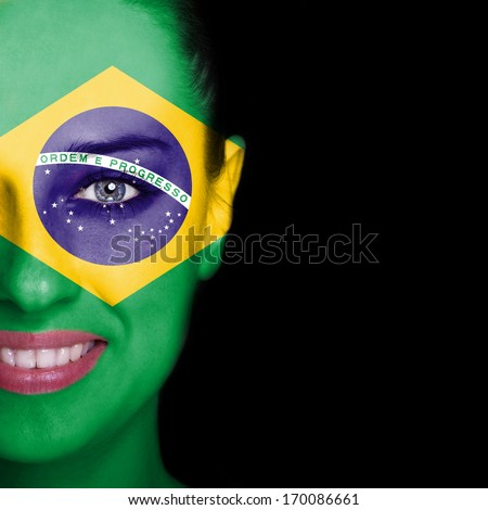 Brazil flag painted on smiling woman face - stock photo