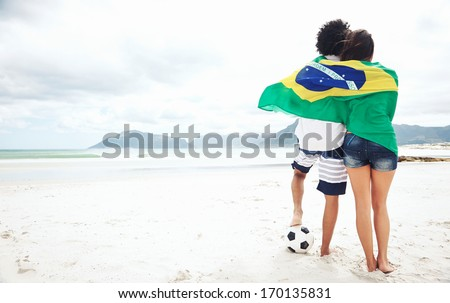 Brazil soccer fans stand on beach together with flag for world cup with ball - stock photo