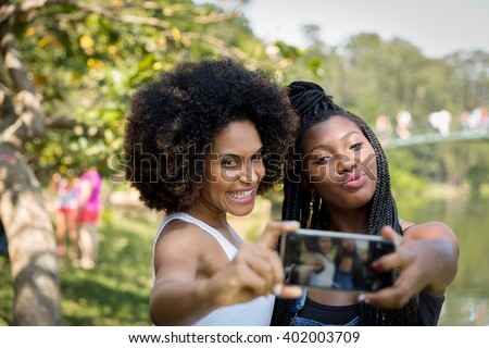 Brazilian afro women taking selfie photos in the park - stock photo