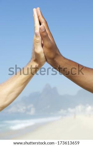 Brazilian diversity - interracial hands clapping together at Ipanema Beach, Rio de Janeiro, Brazil. - stock photo