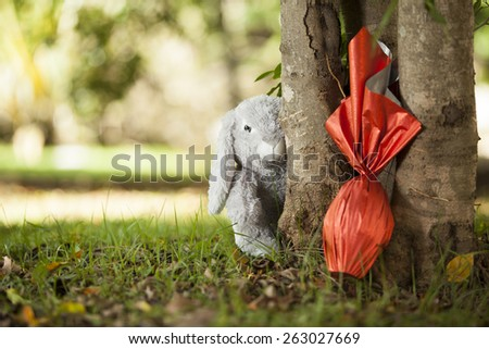 Brazilian Easters egg , wrapped in red paper under a tree, with a bunny in the background. - stock photo
