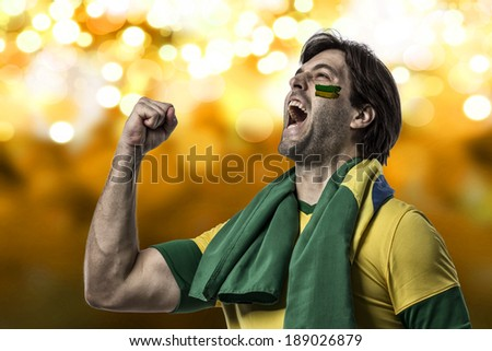 Brazilian fan with paint on his face celebrating on a yellow lights background. - stock photo