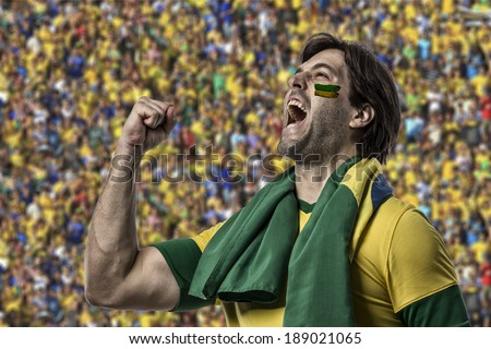 Brazilian fan with paint on his face celebrating with more fans. - stock photo