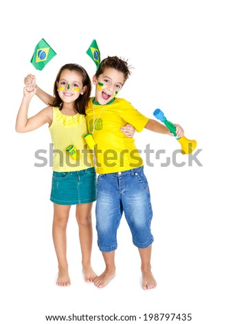 Brazilian fans Kids celebrating and supporting Brazil with vuvuzelas and wearing the colors of Brazil. - stock photo